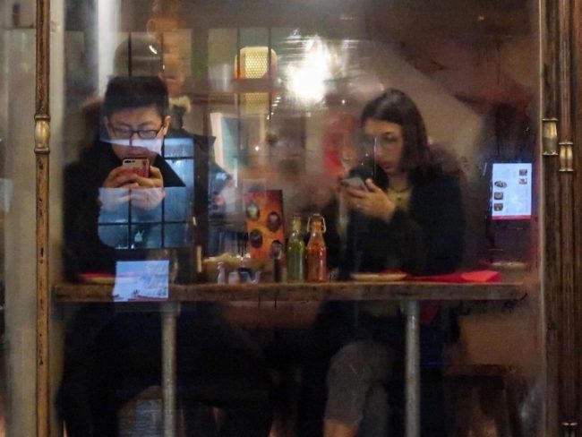 A woman and a man, both wearing glasses and warm jackets, are sitting inside a restaurant window facing the outside world but both looking down on their phones. The glass is foggy and makes an interesting blur on their faces and reflects some streetlights from outside.