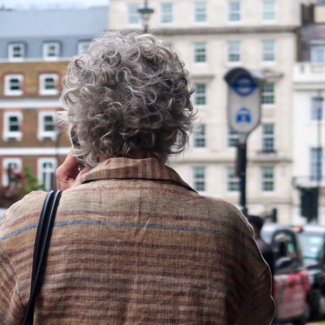 A woman with short grey curly hair is walking away from the camera, holding a phone to her ear, towards London buildings
