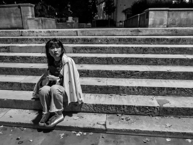 A black and white image of a woman sitting on stone steps littered with leaves or rubbish. Her trench coat is draped across her shoulders and she is looking out to the distance.